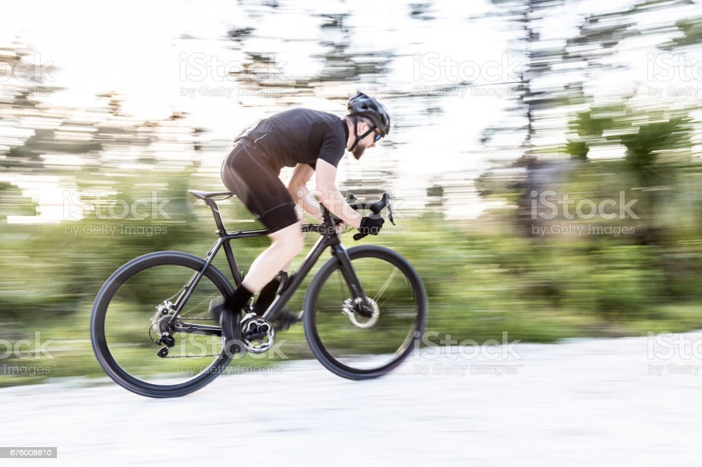 Athlete bicyclist in motion panning shot stock photo