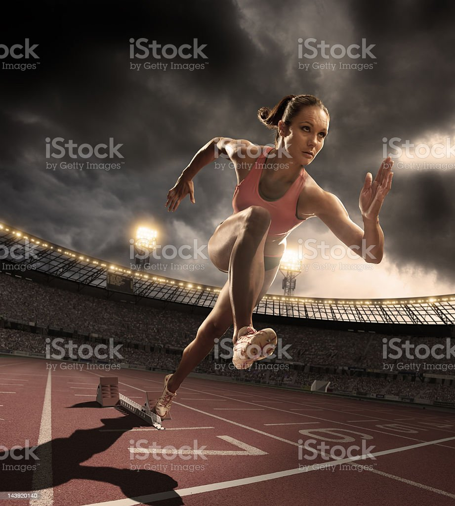 Athlete Bursts Out of Starting Blocks stock photo