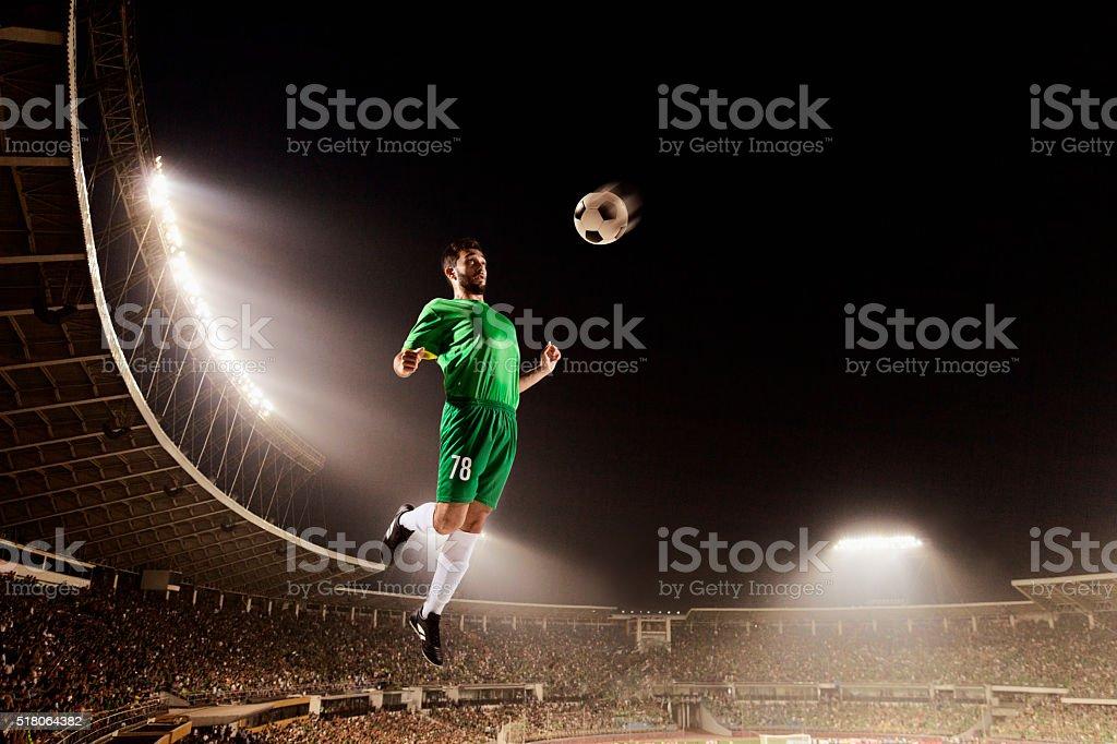 Athlete chesting soccer ball in stadium stock photo
