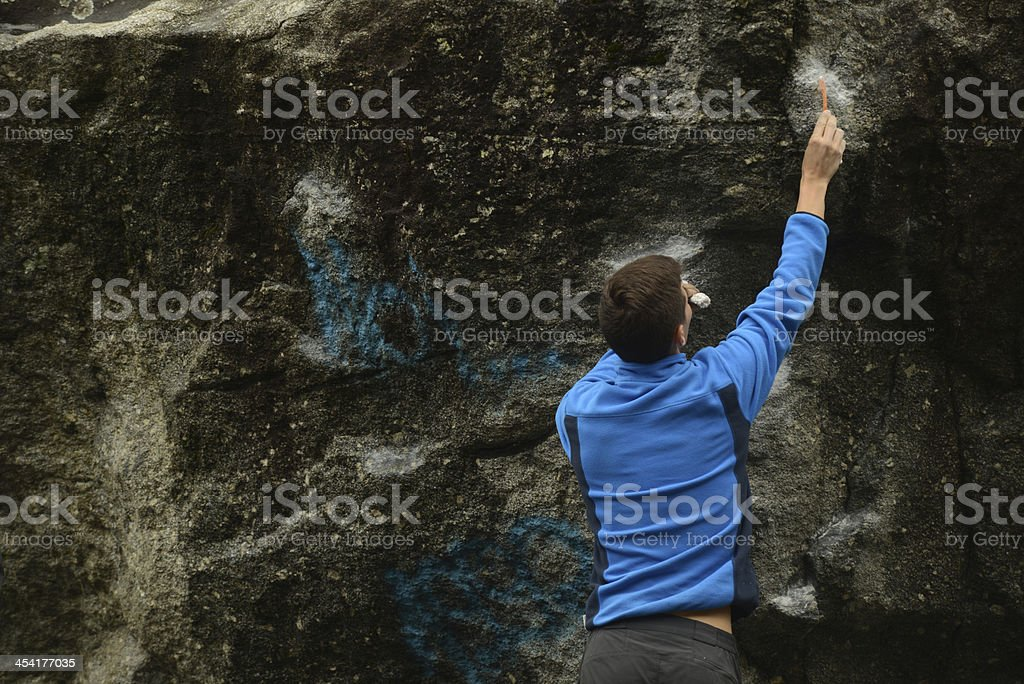 Athlete cleaning up a boulder during competition in Italy royalty-free stock photo