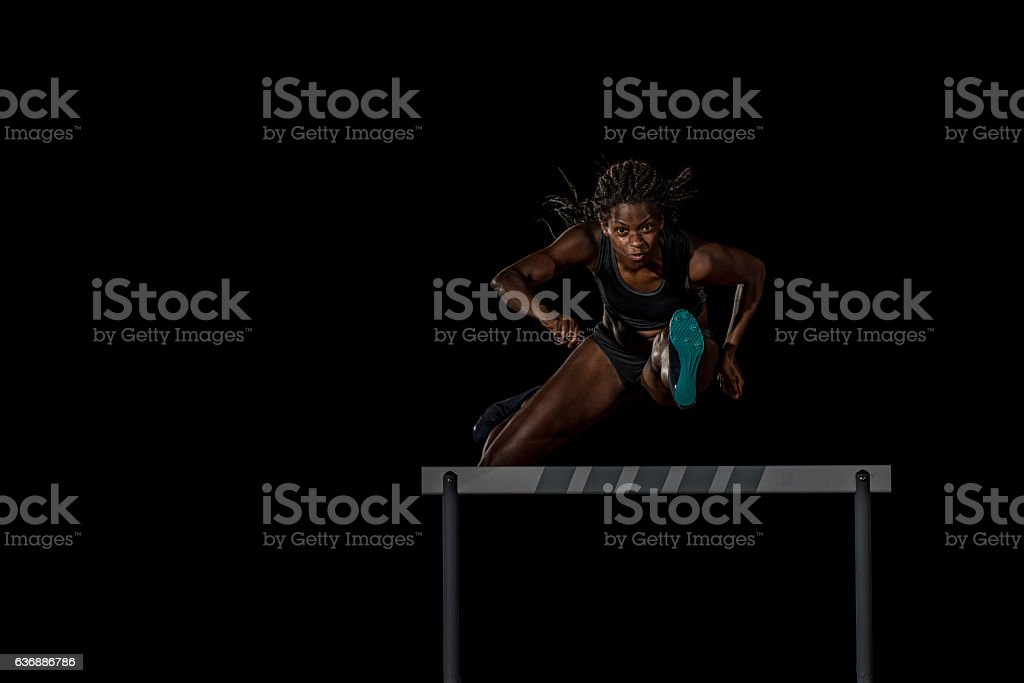 Athlete clearing hurdle stock photo