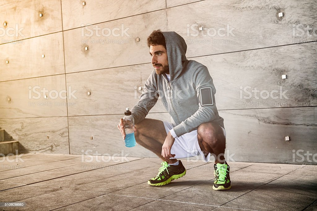Athlete crouched with a sport drink stock photo