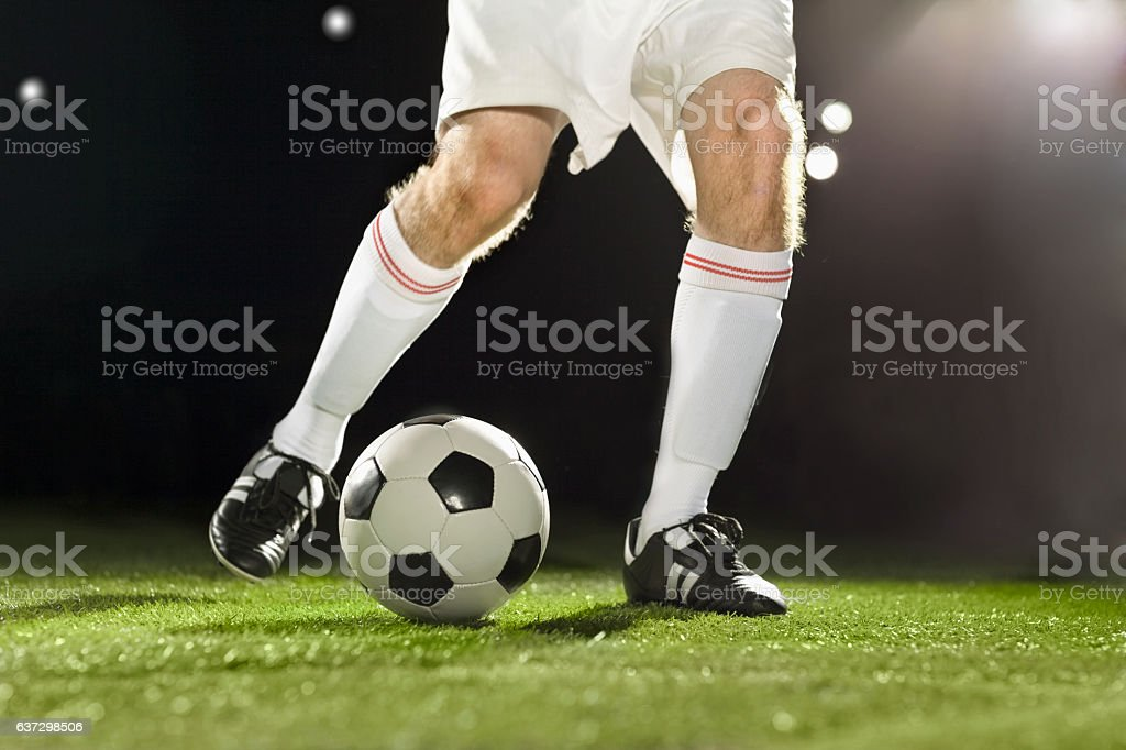 Athlete dribbling soccer ball on field stock photo