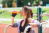 Athlete drinking energy drink after morning jogging in park