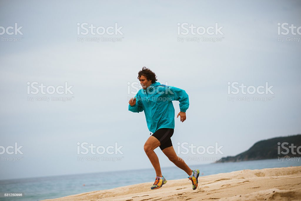 Athlete exercies in morning training, jogging on beach stock photo