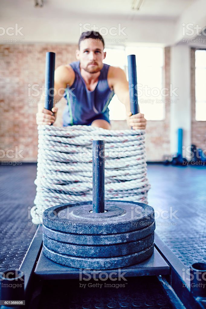 Athlete exercising on battling rope sled in gym stock photo