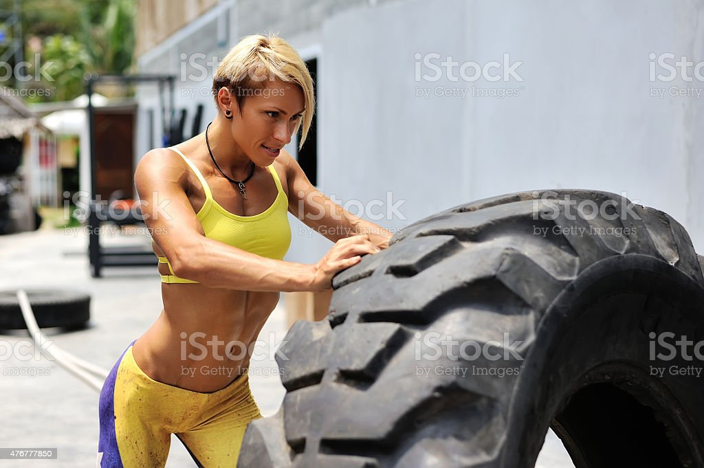 Athlete female working out with a huge tire stock photo