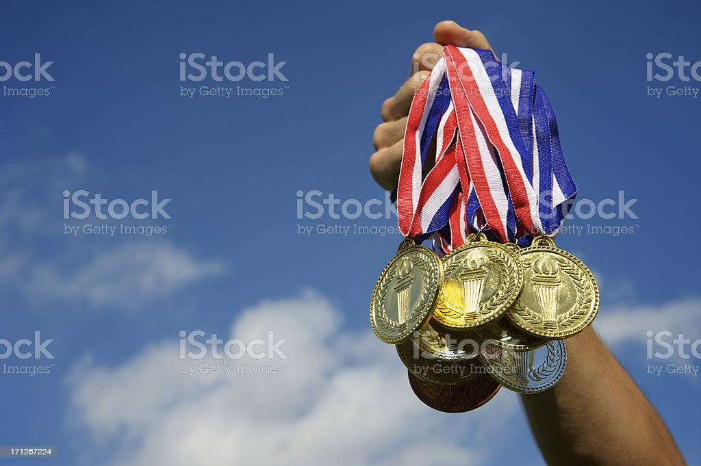 Athlete Hand Holding Up Bunch of Gold Medals Blue Sky stock photo