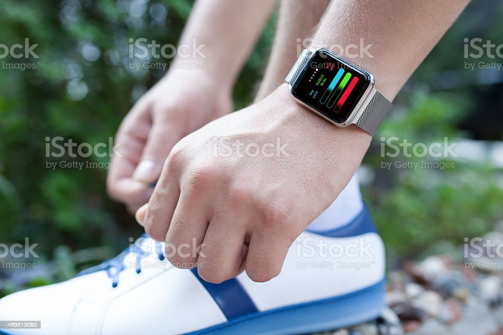 Athlete hand with watch and app training on the screen stock photo