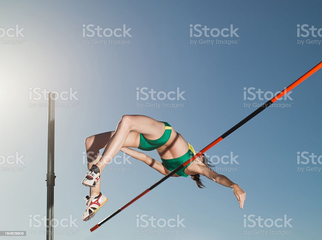 Athlete high jumping in an arena stock photo