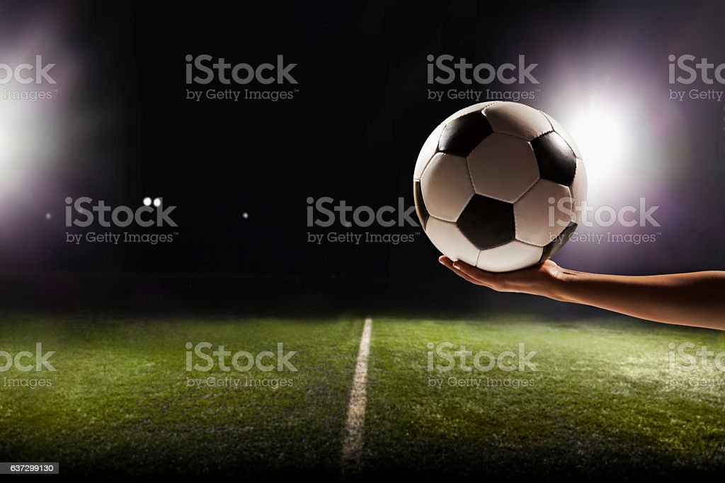 Athlete holding soccer ball at sports field stock photo