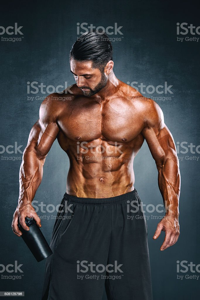 Athlete holding Supplement Nutrition Bottle stock photo