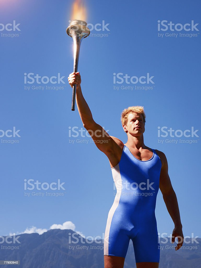 Athlete holding torch in scenic location royalty-free stock photo