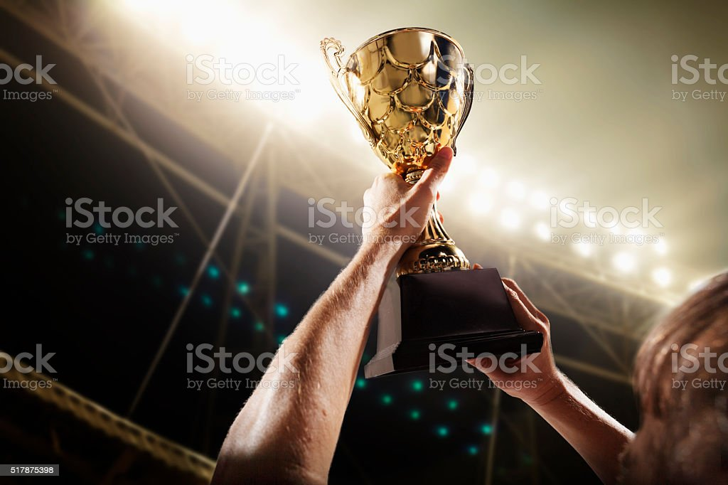 Athlete holding trophy cup stock photo