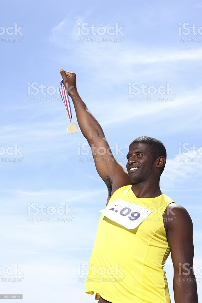 Athlete holding up medal royalty-free stock photo