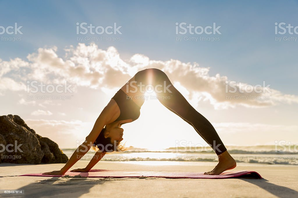 Athlete in downward facing dog position on shore stock photo