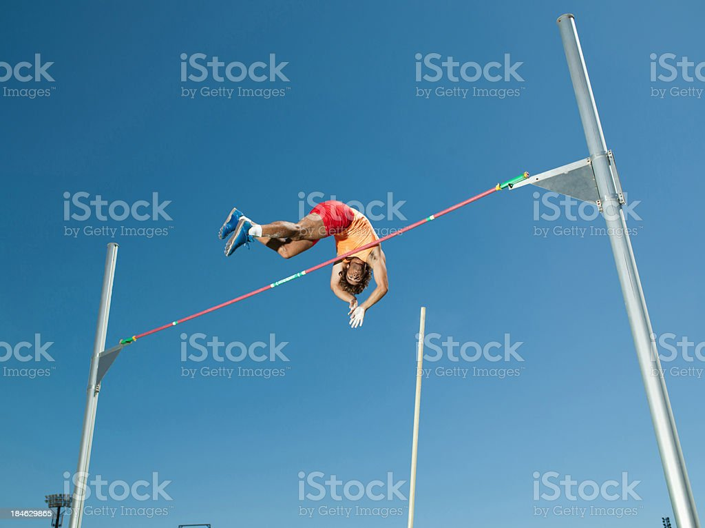 Athlete in mid air doing pole vault stock photo