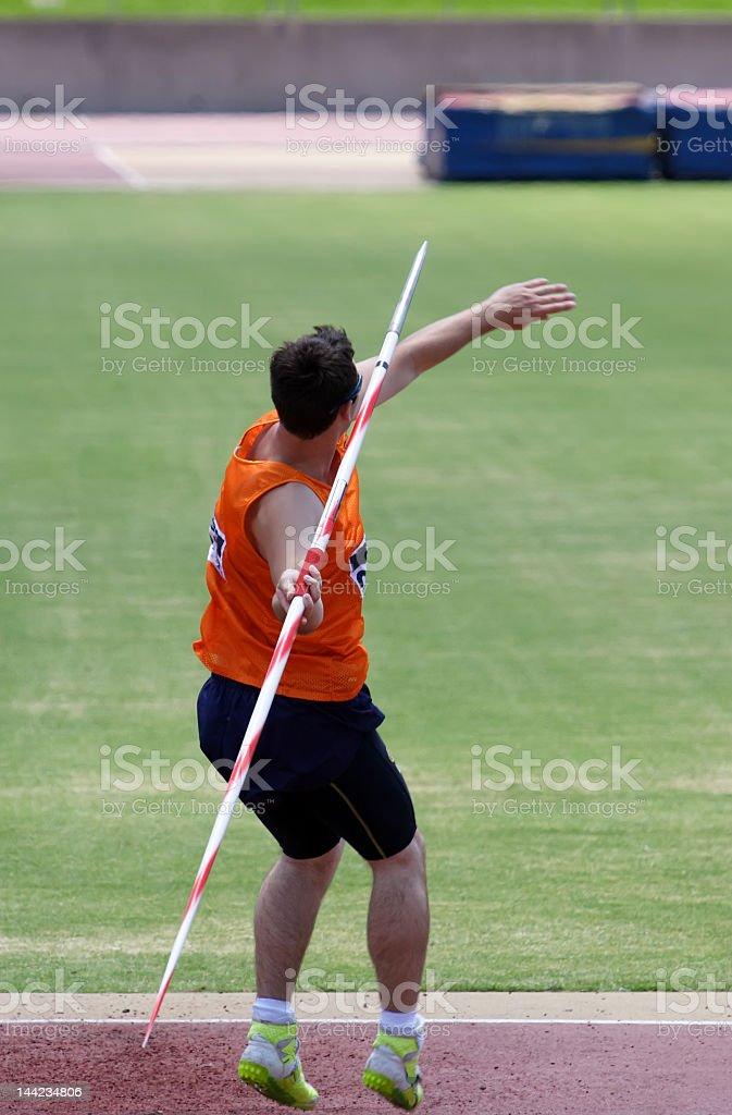 Athlete in orange singlet throwing javelin stock photo