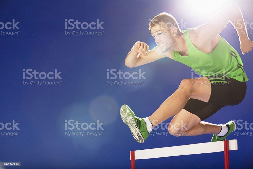 Athlete jumping hurdles royalty-free stock photo