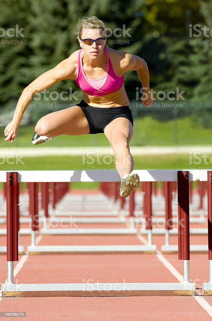 Athlete Jumping Over Hurdles on a Track stock photo