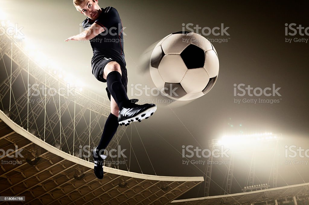 Athlete kicking soccer ball in stadium stock photo