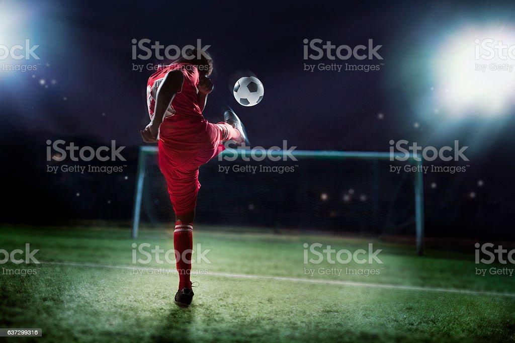 Athlete kicking soccer ball into a goal stock photo