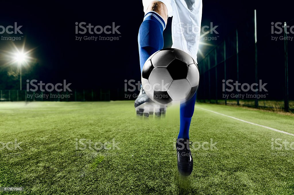 Athlete kicking soccer ball stock photo