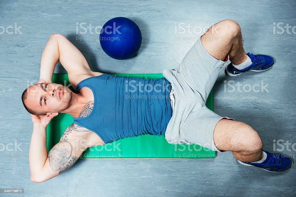 Athlete man doing sit ups for abdominal muscles in gym stock photo