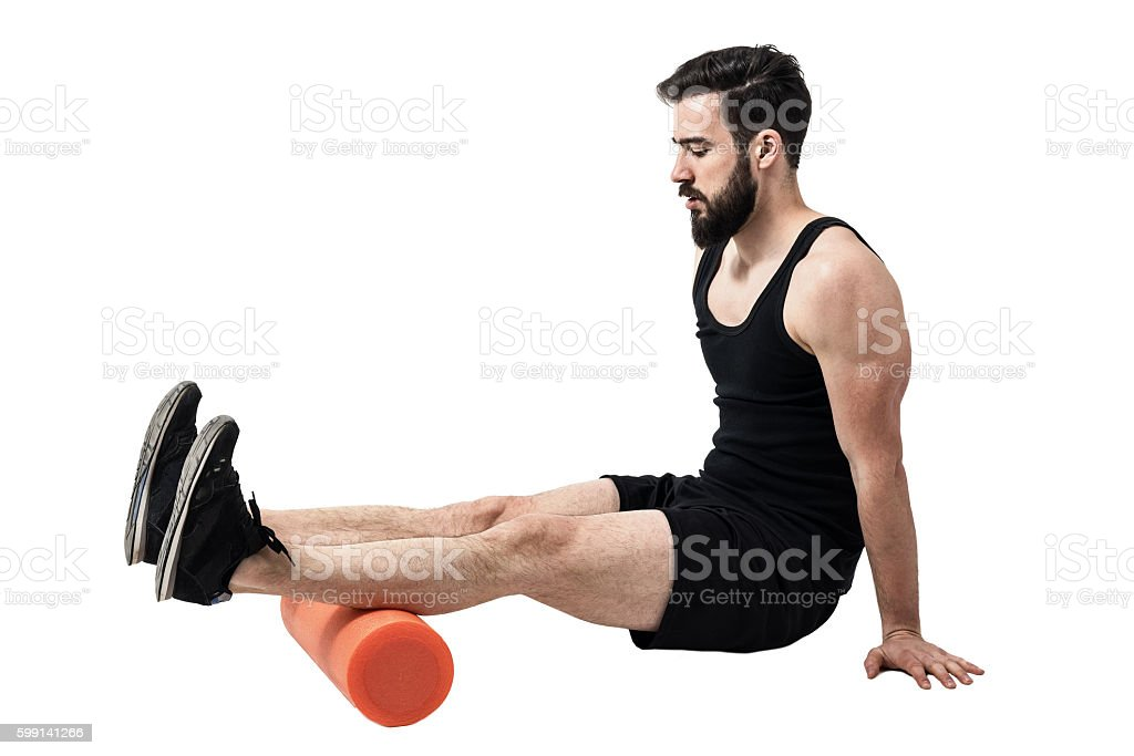 Athlete massaging and stretching hamstring leg muscles on foam roller stock photo