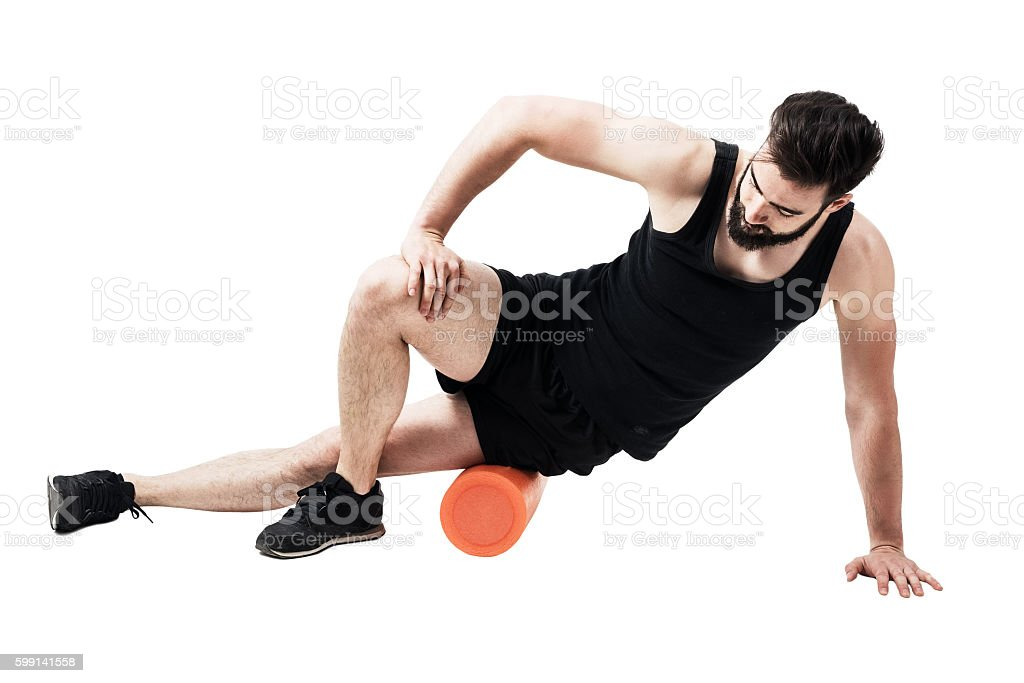 Athlete massaging and stretching iliotibial band muscle with foam roller stock photo