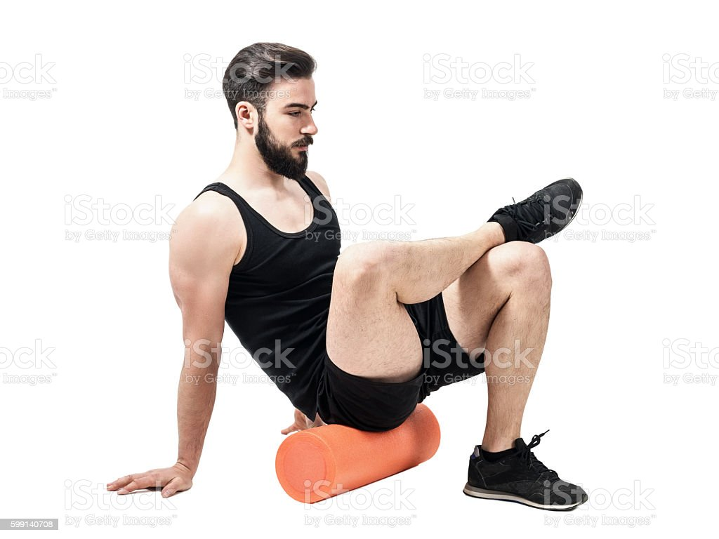 Athlete massaging glutes muscles with foam roller. stock photo