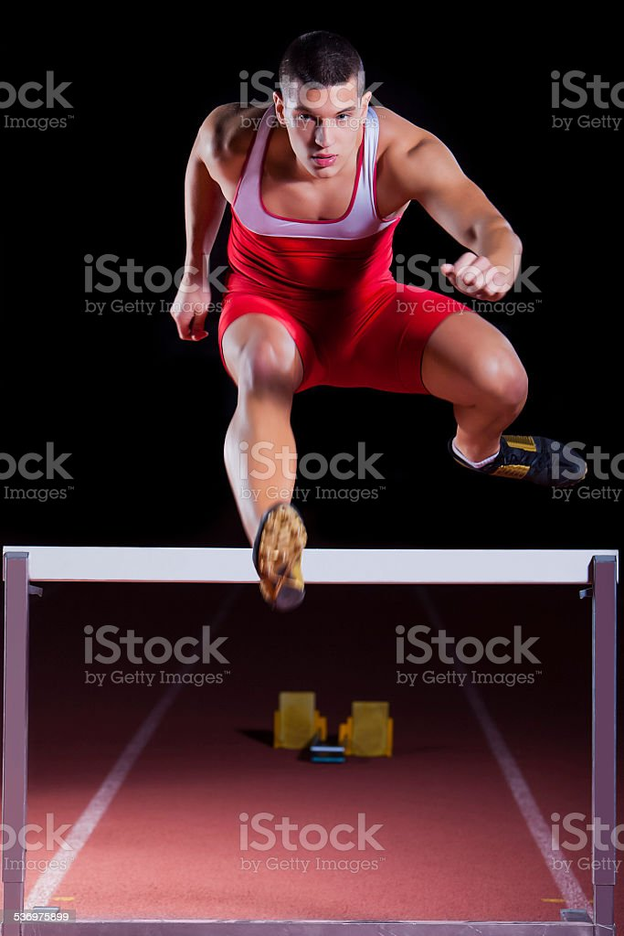 athlete on hurdle in track and field stock photo