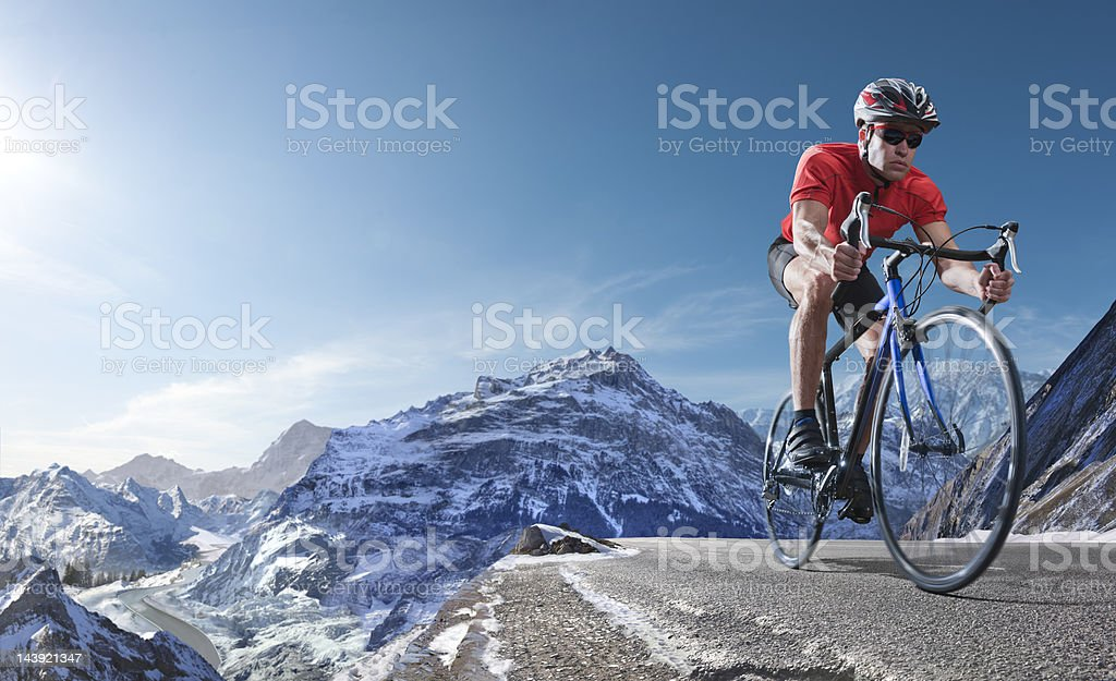 Athlete On Racing Bike Cycling Through Alpine Mountains stock photo