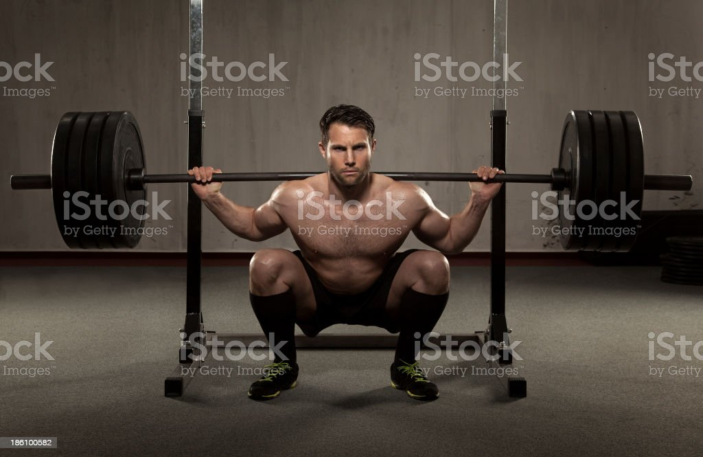 Athlete performing squat with barbell stock photo