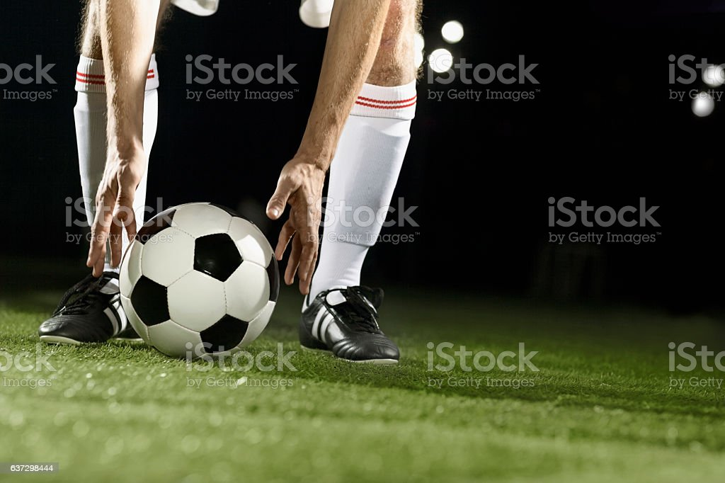 Athlete placing soccer ball for corner kick on field stock photo