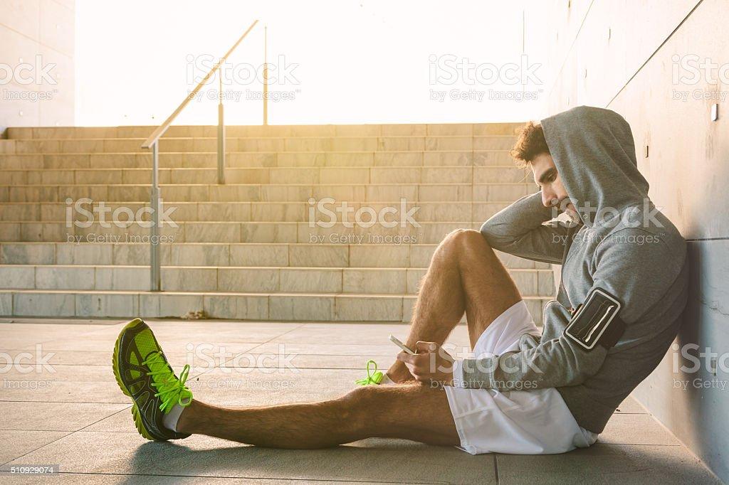 Athlete resting near a stadium entrance stock photo