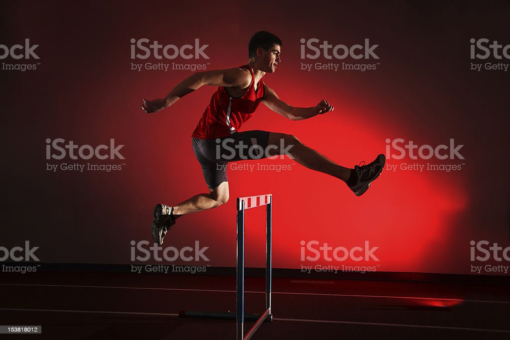 athlete running hurdles isolated on red background stock photo