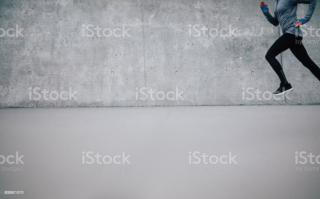 Athlete running on gray background stock photo