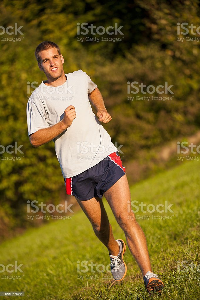 Athlete running on the meadow stock photo