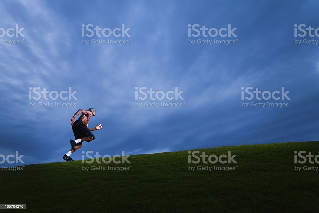 Athlete running up grassy hill royalty-free stock photo