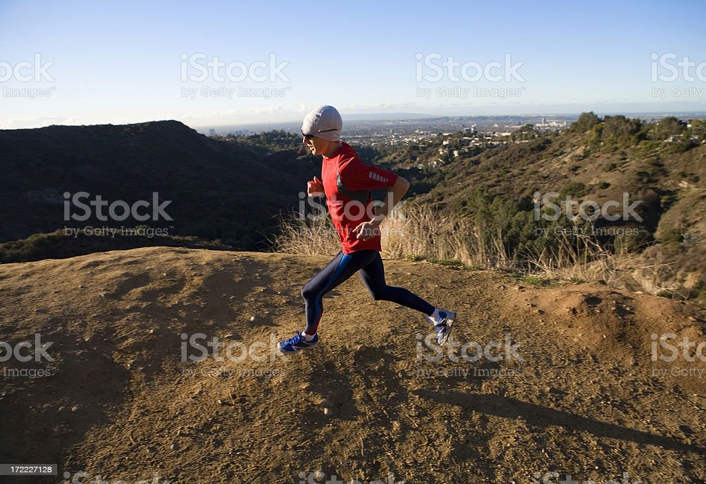 Athlete runs in hills overlooking Los Angeles stock photo