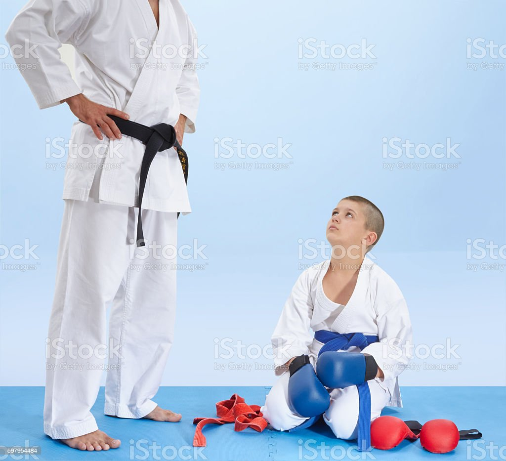 Athlete sitting on mat listening to the instruction of coach stock photo
