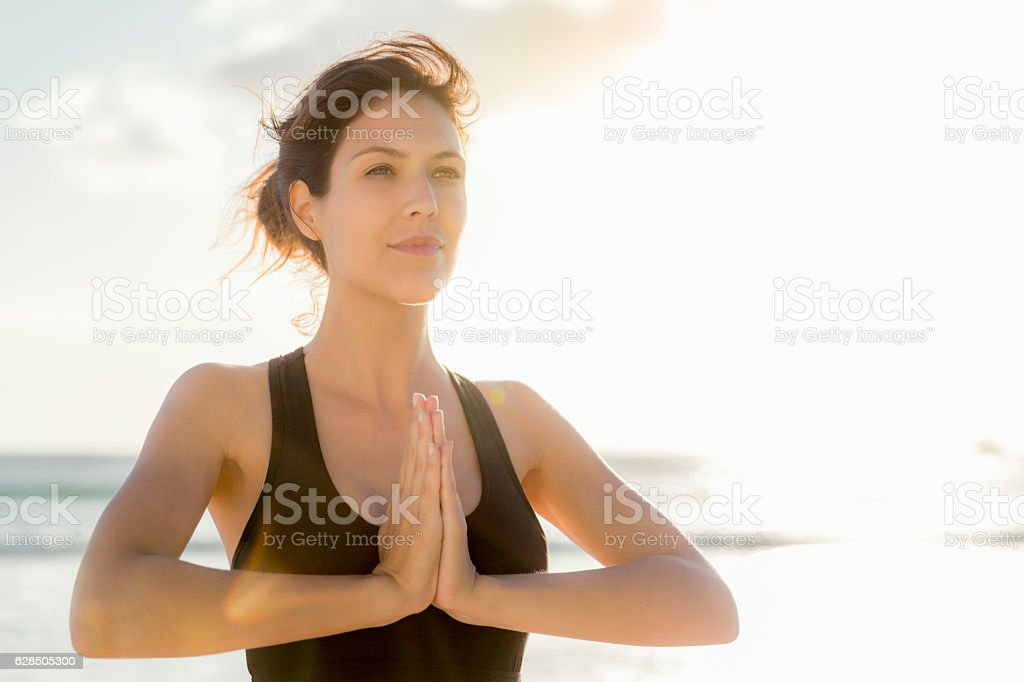 Athlete standing in prayer position at beach stock photo