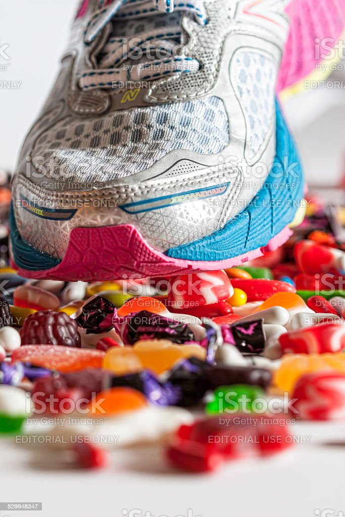 athlete stepping candy.anti-obesity, against refined, processed sugar stock photo