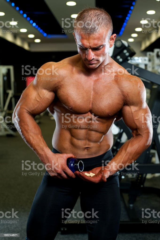 Athlete taking his supplement pills royalty-free stock photo