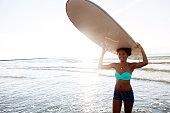 Athlete teenage girl carries surfboard into ocean