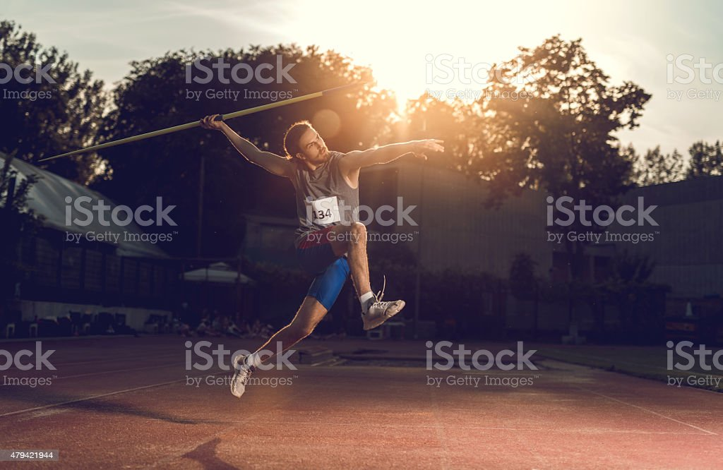 Athlete throwing a javelin on a stadium at sunset. stock photo