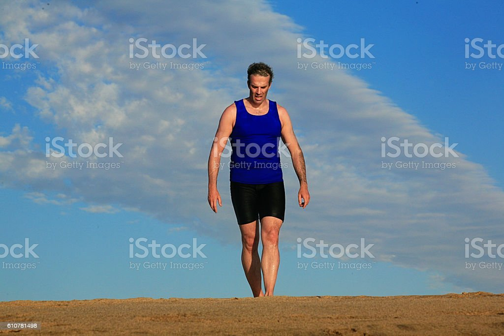 Athlete trains on a sand dune stock photo