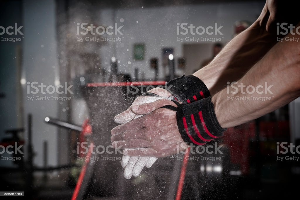 Athlete uses talc in the gym stock photo