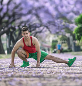 Athlete warming up stretching in park outdoors